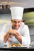 Smiling male chef with cooked food in kitchen — Stock Photo