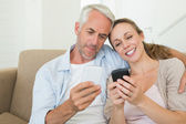Happy couple sitting on couch texting on their phones — Stock Photo