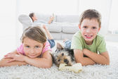 Siblings lying on rug with yorkshire terrier smiling at camera — Stock Photo