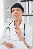 Thoughtful female doctor writing on clipboard — Stock Photo