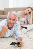Smiling couple lying on rug playing video games — Stock Photo
