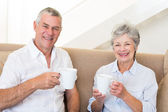 Senior couple sitting on couch drinking coffee smiling at camera — Stock Photo