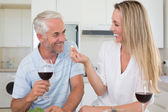 Cheerful couple preparing dinner together and drinking red wine — Stock Photo
