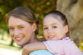 Happy mother and daughter at park — Stock Photo