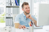 Smiling man working at his desk — Stock Photo