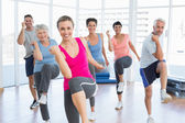 Smiling people doing power fitness exercise at yoga class — Stock Photo