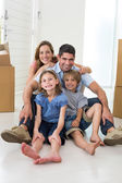 Family sitting on floor in new house — Stock Photo