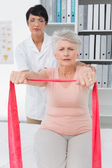Female physiotherapist massaging senior womans back — Stock Photo