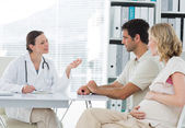 Dynaecologist discussing with expectant couple — Stock Photo