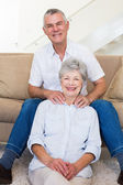 Man giving his relaxed senior wife a shoulder rub smiling — Stock Photo