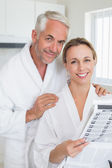 Happy couple reading newspaper together in bathrobes — Stock Photo