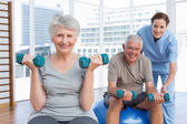 Female therapist assisting senior couple with dumbbells — Stock Photo