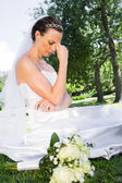 Depressed bride sitting in garden — Stock Photo