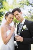 Bride and groom holding champagne flutes — Stock Photo