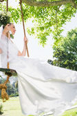 Thoughtful bride swinging in garden — Stock Photo