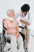 Doctor talking to a senior patient with cervical collar — Stock Photo