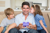 Father receiving gift from loving children — Stock Photo