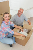 Happy couple unpacking cardboard moving boxes — Stock Photo
