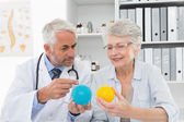 Doctor showing stress buster balls to senior patient — Stock Photo