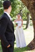 Happy bride looking at groom in garden — Stock Photo