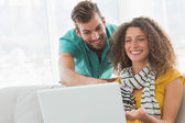 Smiling woman showing her co worker her laptop — Stock Photo