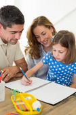 Parents assisting daughter in coloring — Stock Photo