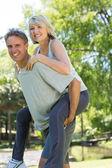 Man giving piggyback ride to woman — Stock Photo