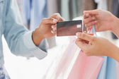 Mid section of customer receiving shopping bags and credit card  — Stock Photo