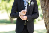 Groom adjusting sleeve in garden — Stock Photo