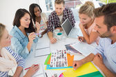Young design team going over contact sheets at a meeting — Stock Photo