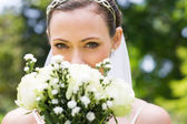 Bride peeking over bouquet in garden — Stock Photo