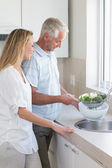 Couple rinsing vegetables at the sink — Stock Photo