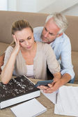 Serious couple calculating their bills at the couch — Stock Photo