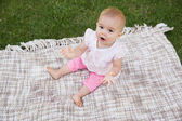 Portrait of a cute baby on blanket at park — Stock Photo