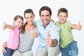 Cute family smiling at camera together showing thumbs up — Stock Photo