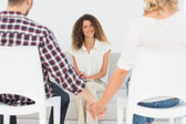 Happy therapist smiling at reconciled couple holding hands — Stock Photo