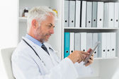 Concentrated doctor using digital tablet at medical office — Stock Photo