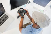 Photo editor looking at digital camera in office — Stock Photo