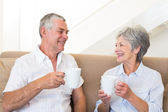 Senior couple sitting on couch drinking coffee — Stock Photo