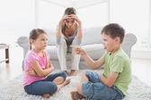 Fed up mother listening to her young children argue — Foto Stock
