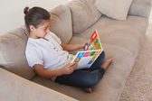 Relaxed girl reading storybook — Stock Photo