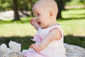 Cute baby sitting on blanket at park — Stock Photo