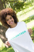 Environmentalist holding volunteer tshirt — Stock Photo