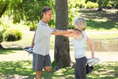 Couple stretching legs in park — Stock Photo