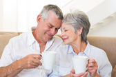 Senior couple sitting on couch drinking coffee touching heads — Stock Photo