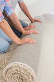 Couple rolling out new rug — Stock Photo