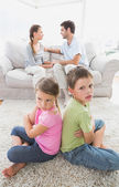 Pouting siblings sitting back to back while parents are arguing — Stock Photo