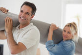 Couple carrying rolled rug — Stock Photo
