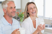 Laughing couple having coffee together — Stock Photo