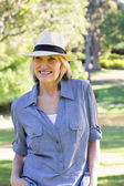 Happy woman wearing sunhat in park — Stock Photo